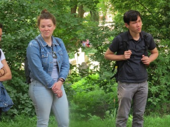 Students, Chenda and Annika, listen to our study tour guide at an important cemetery in Warsaw.